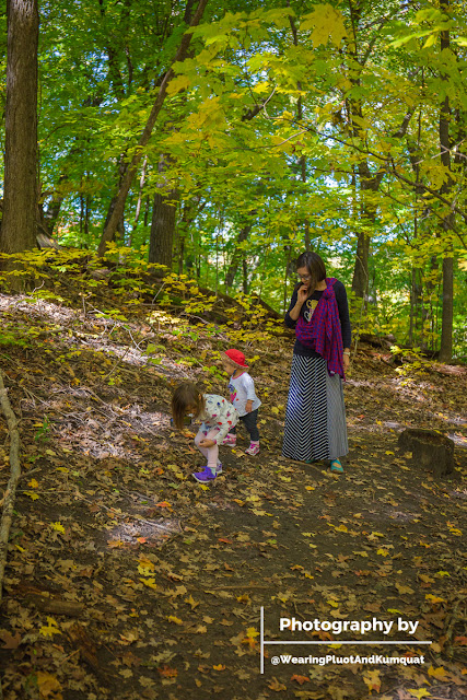 Image of a tan skin bespectacled Asian woman with a red and blue checked woven wrap carrier tied in a one-shouldered carry. Next to her are two children. The three of them are exploring in a forest surrounded by green and yellow foliage of autumn.