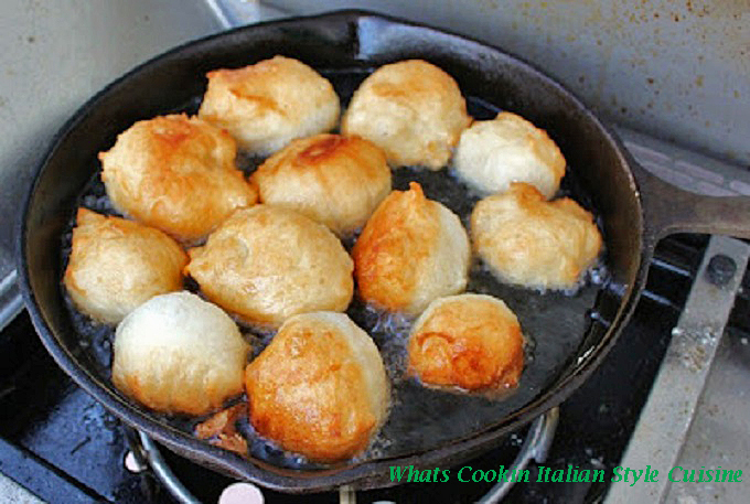 This is a cast iron pan frying donuts for St. Joseph's Day celebrations at feasts outdoors on a grill