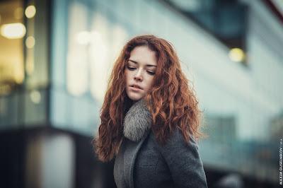 Linda chica pelirroja en la ciudad con abrigo