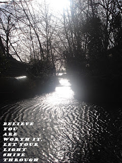 Image of sunlight streaming through trees in silhouette onto water with text: Believe you are worth it. Let your light shine through