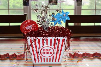 Centro de mesa hecho con caja de pop corn, estrellas y golosinas.