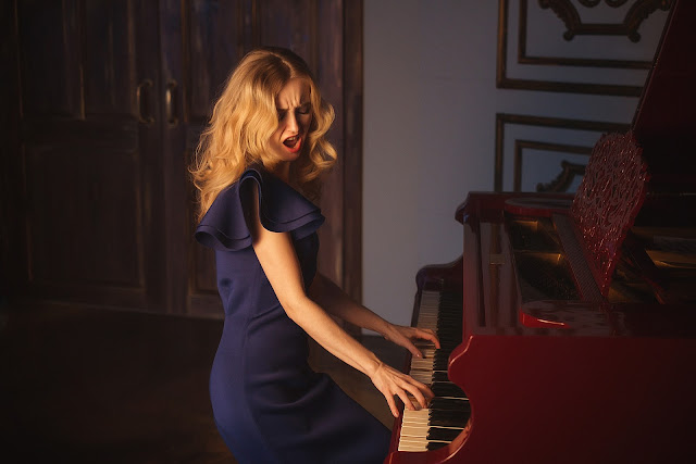 a female singer singing and playing the piano.