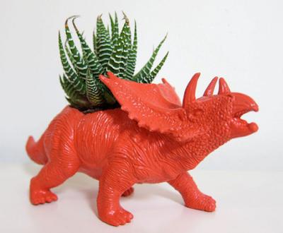 Dinosaurio de plastico convertido en maceta
