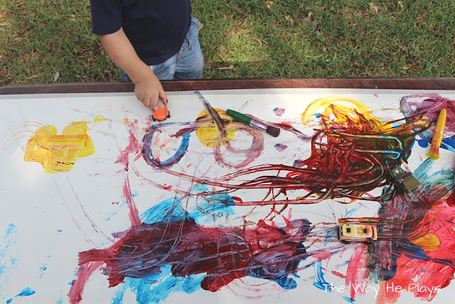 Toddler painting with cars