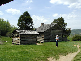 Notice the original log cabin side is apparent on the house, with later milled lumber porch and kitchen additions on either side.