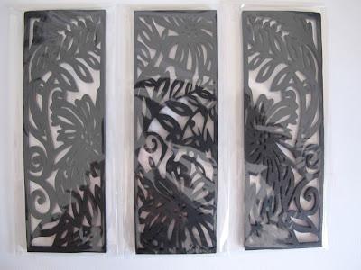 Three laser-cut wooden bookmark-sized black panels with Australian flora designs.