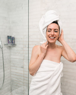 A woman smiling in the mirror wrapped in a towel