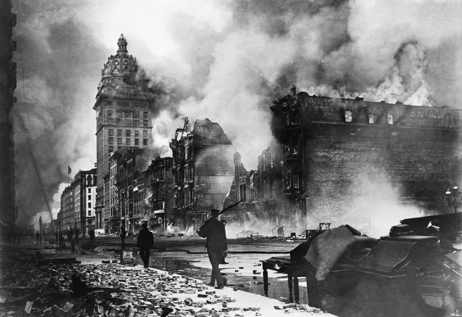 Troops walk east along Market Street after the devastating earthquake of 1906. The Call building burns in the distance