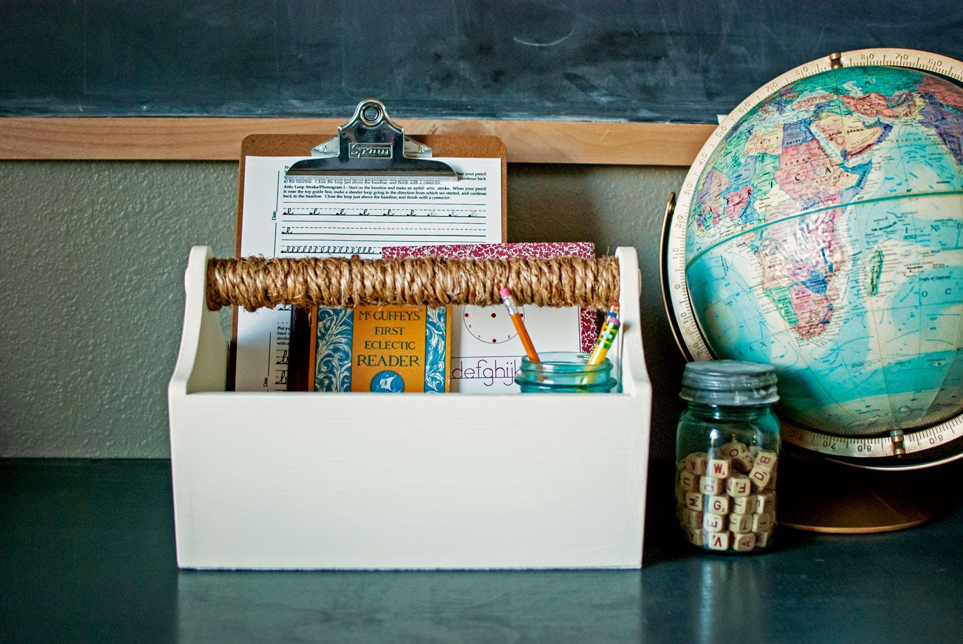 Farmhouse Tool Box With School Supplies Inside Next to a Vintage Globe