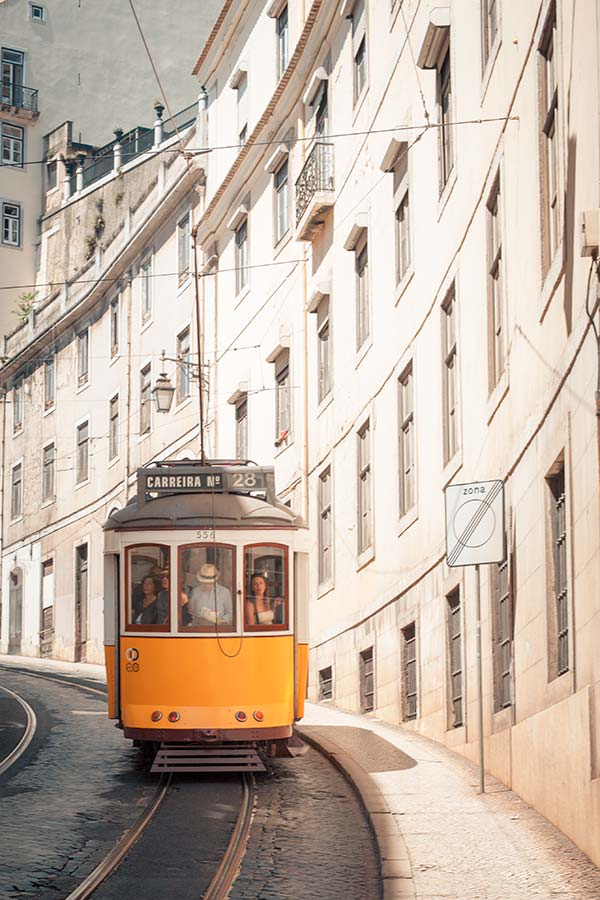 The famous yellow Tram 28 ascending a steep street in Lisbon, Portugal
