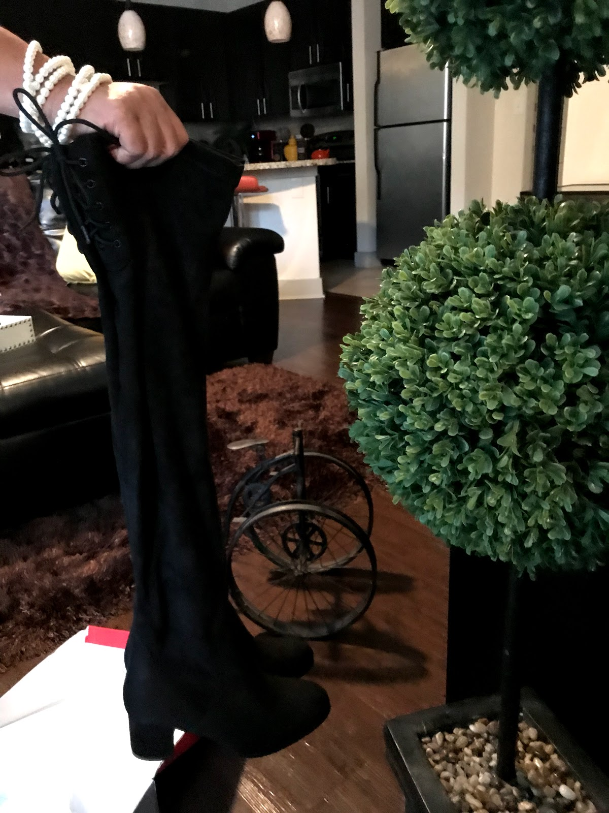 Image: Woman holding unboxing and showing off new over the knee boots from Amazon