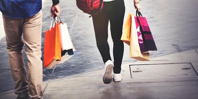Homem e mulher segurando sacolas de compras