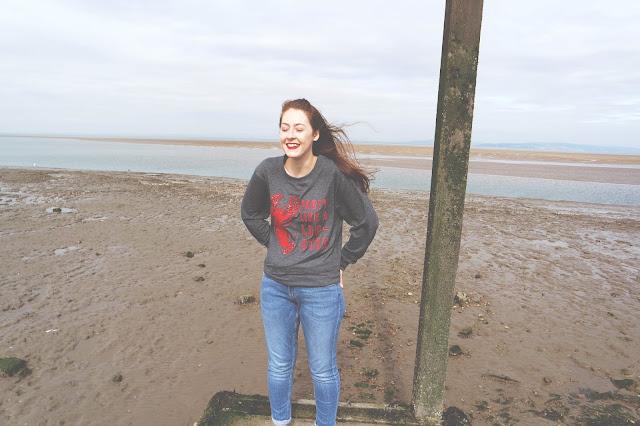 Lyd standing on a pier with the beach behind her, wearing blue jeans, a grey jumper with a red lobster, and red lipstick. She is smiling with her eyes closed.