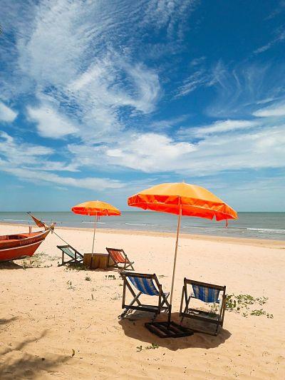 Playa: dos sombrillas en la arena. Dos reposeras debajo de cada una. Entre ambas sillas, una pequeña mesa. Al lado se ve parte de un bote