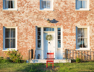 Red chair in front of front porch at historic Woodlawn Farm, a two story brick structure with a wreath on the white front door