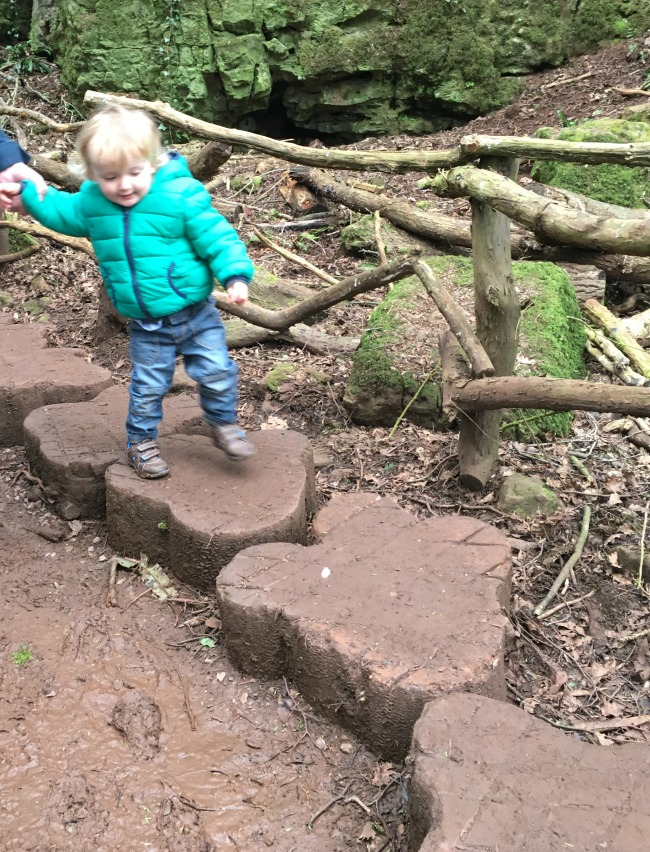 toddler holding adults hand and walking on dinosaur footprints