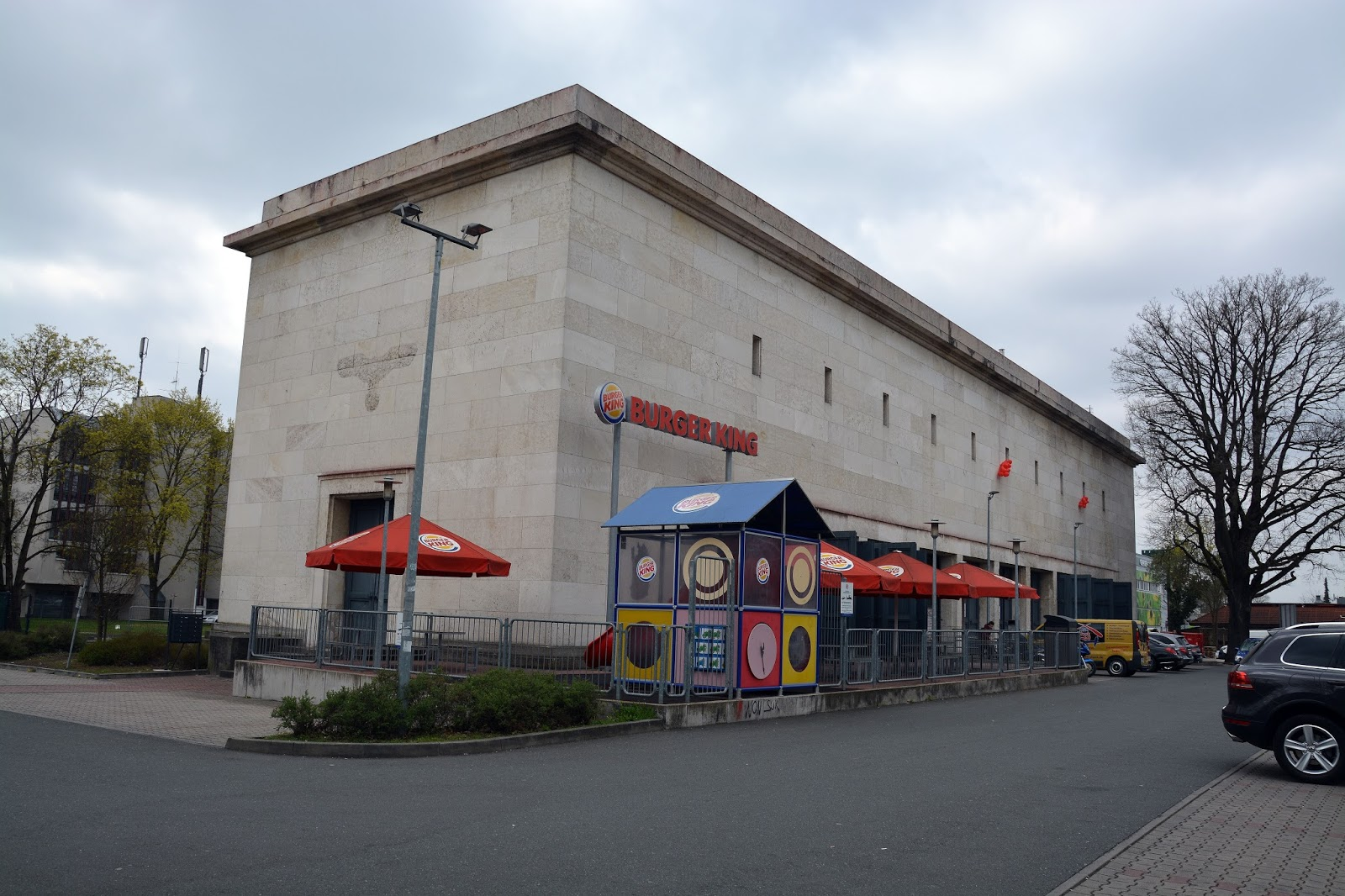 In Nuremberg, there's a Burger King in a former Nazi transformator building:  https://3.bp.blogspot.com/-Le8-DNy_Mt4/WOgwkp9NTkI/AAAAAAAAfdc/XGG78vKUSgwOfsN1xXT0wpHwgi43Eju0ACLcB/s1600/DSC_0718.JPG  Take that, evil McDonald's!