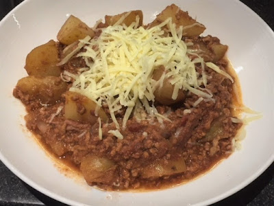 Slow Cooker Bolognese and Potato Hash in a bowl topped with cheese