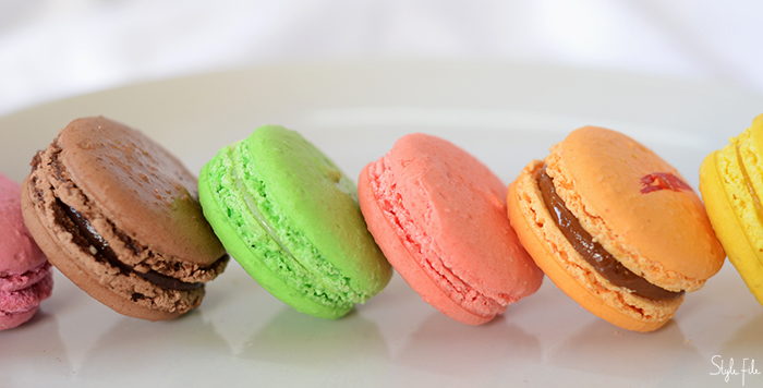 An image of macarons in flavours of chocolate, pistachio, caramel and strawberry on a white background being served for dessert