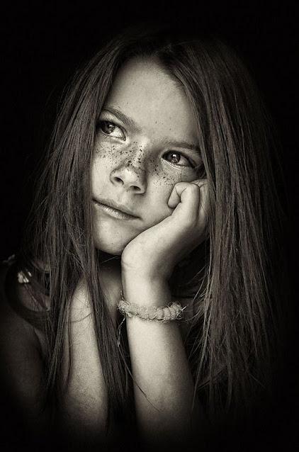 Retratos em preto e branco de uma menina com sardas chamada Laura olhando para o lado e com as mãos no queixo