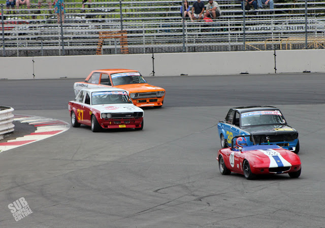 A Lotus Elan and several Datsun 510 race cars at PIR