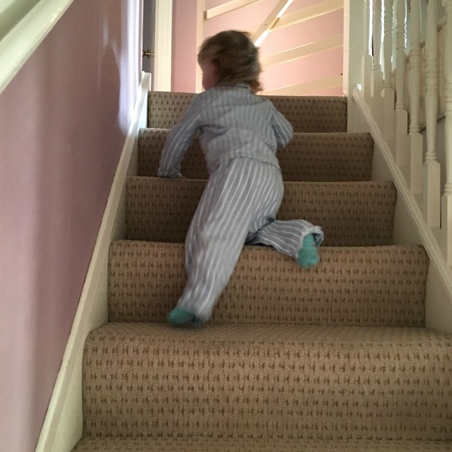 toddler in pyjamas climbing stairs