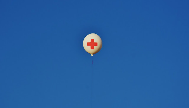 White balloon emblazoned with a red First Aid cross floating against a bright blue sky