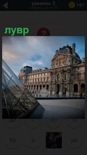 На площади в городе показано здание музея лувр