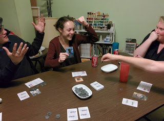 four players sitting around a table, looking animated at the current events of the game, playing Coup. There are cards and tokens on the table, with a bowl of spare tokens in the centre.