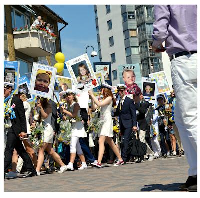 studenter med mössor och plakat