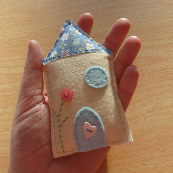 Miniature felt house hand sewn and held in hand