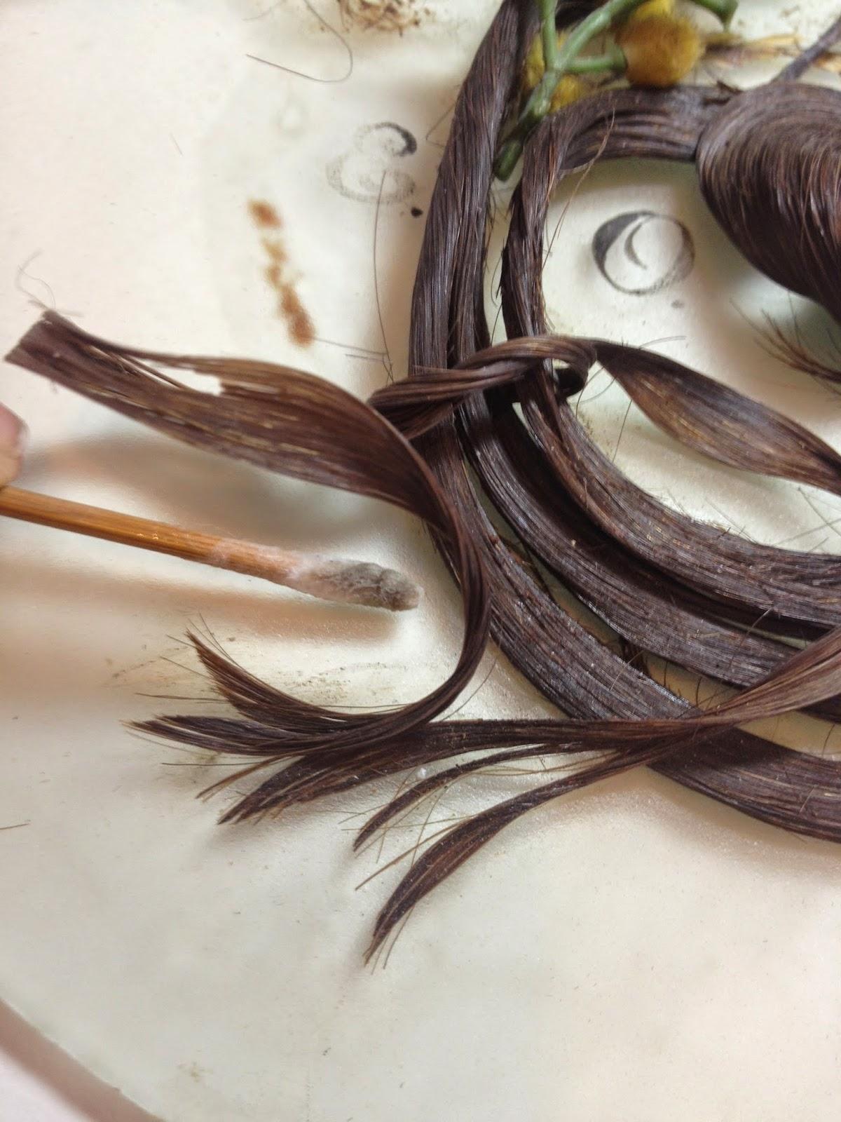 Objects art conservator, Gwen Spicer carefully removes dirt and debris from this Victorian Hair Art