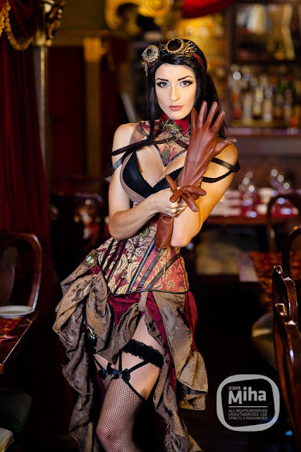Woman wearing a sexy steampunk burlesque dancer costume. Red and brown underbust corset, red and brown high low hem skirt, brown leather gloves, goggles, garters and fishnet thigh high stockings, black bra