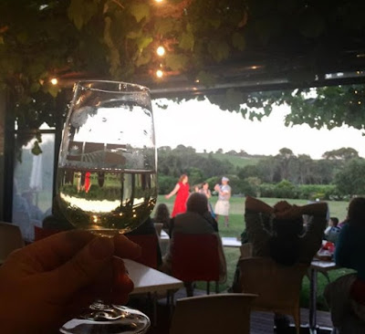 A close up of a wine glass toasting, from under the vines of the verandah, looking out onto the players on the lawn.
