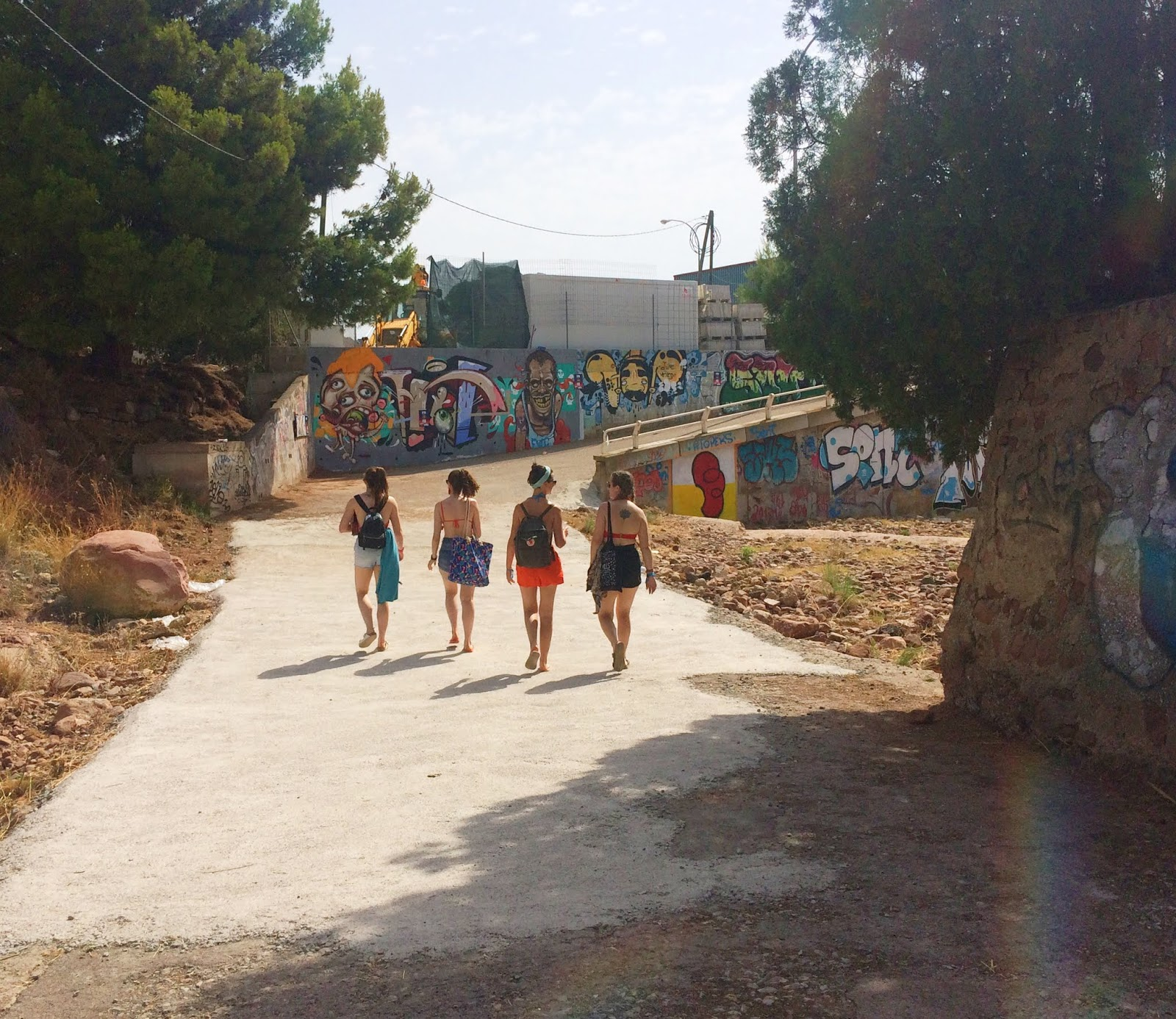 Group of girls walking through graffiti tunnel in Benicasim
