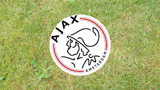 Rood witte Ajax logo op groen gras