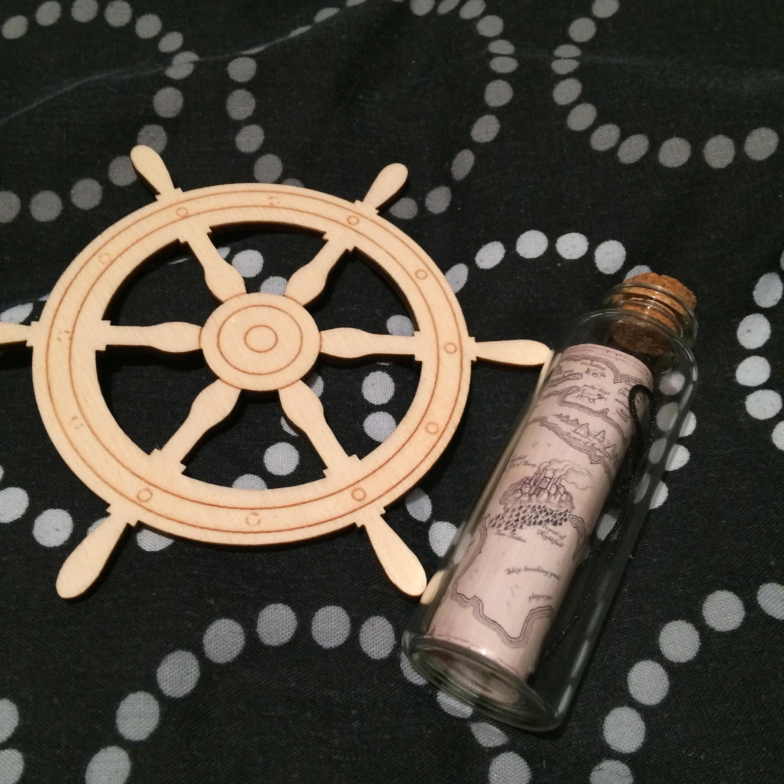 A wooden ship's wheel and a tiny rolled up map inside a corked, glass bottle, for their Songs of the Current