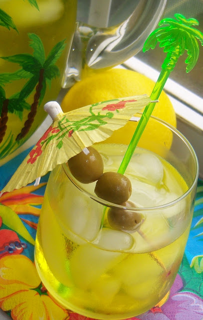 Tropical designed pitcher full of holiday cheer! This is limoncello homemade in a pitcher and glass of tropical island style drink with an umbrella and olives on a tooth pick