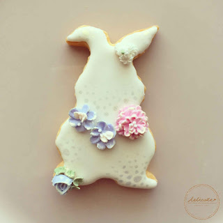 bunny cookie decorated with natural food coloured piped icing flowers