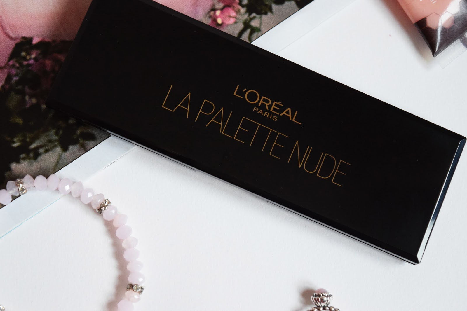a flatlay image of the loreal paris nude rose palette on a white sheet of paper surrounded by jewellery