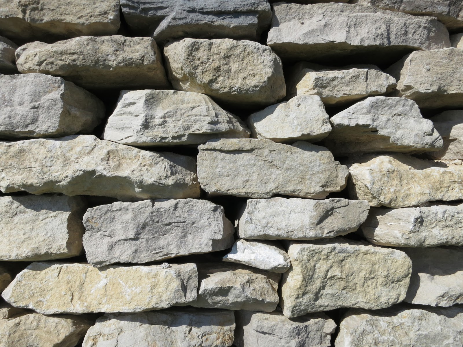 New, dry-stone wall with regular (Portland) stones.