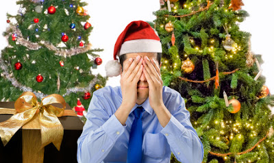 depressed man by christmas tree and presents