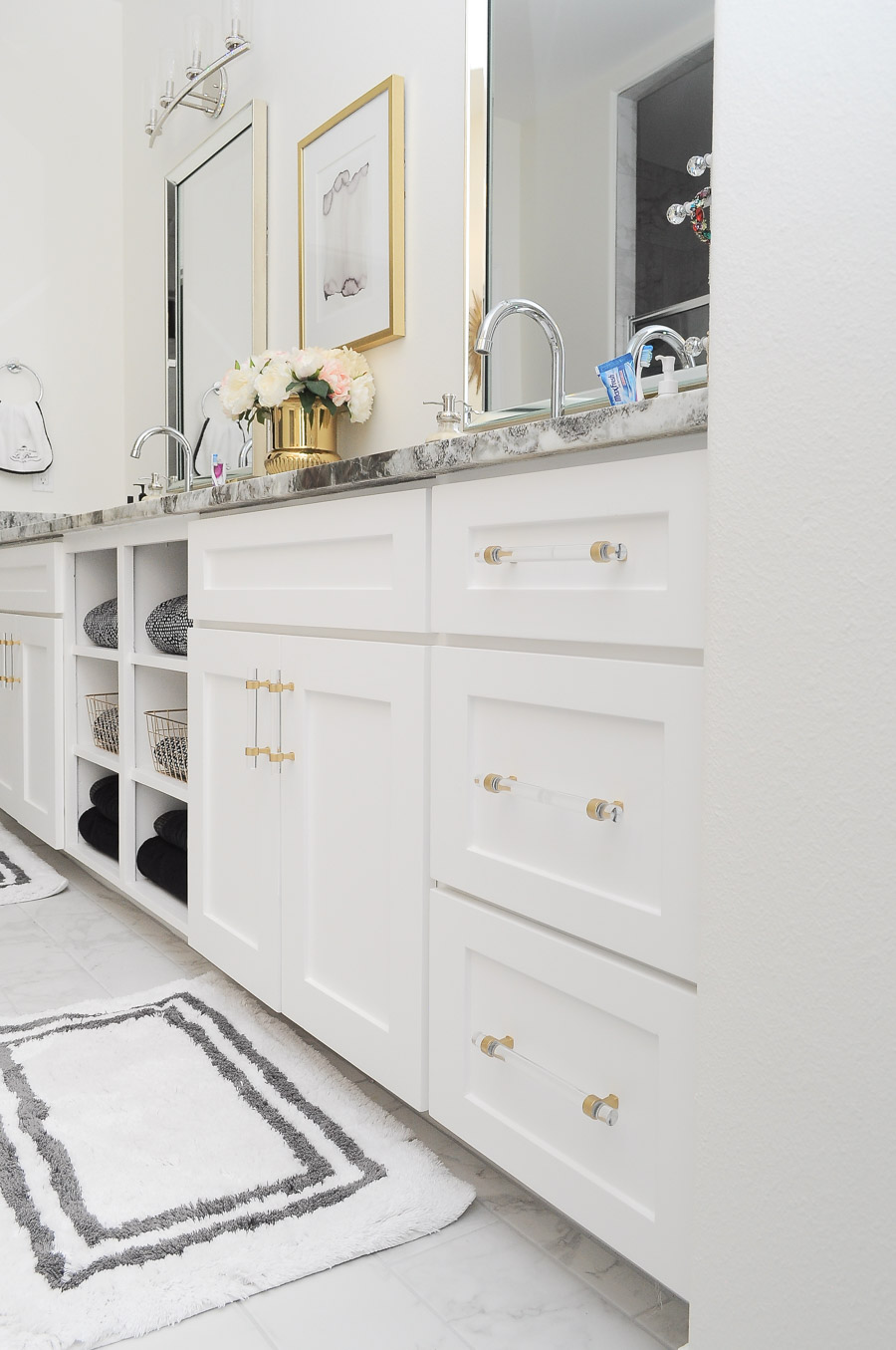 Gold and lucite drawer pulls in a bright white and gold master bathroom.