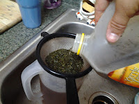 Sifting tea leaves out of homemade tea.