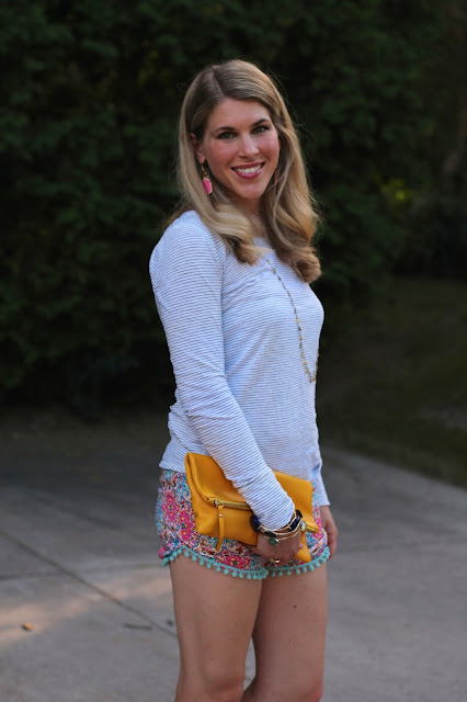 long sleeve striped top, printed pom pom shorts, yellow clutch, wedge sandals