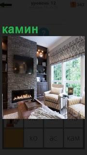 В комнате с большими окнами находится камин и рядом расположена мягкая мебель