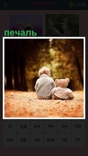 мальчик с игрушкой сидит на дороге в печали
