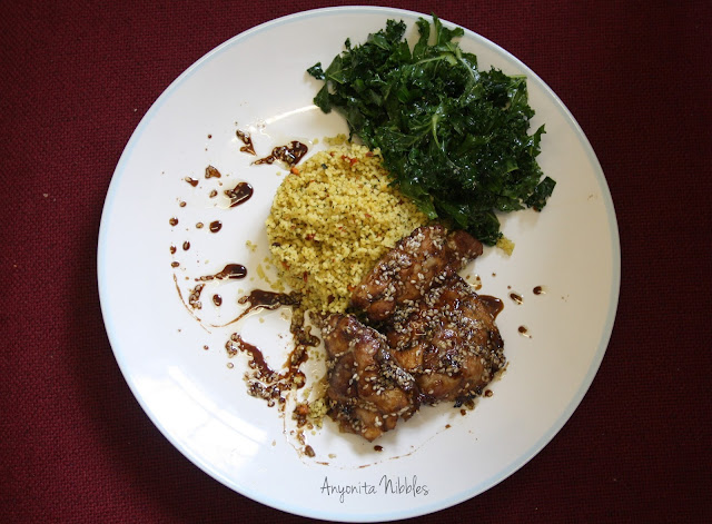 A plate of sweet & hot baked sesame chicken with couscous and raw kale salad from www.anyonita-nibbles.com