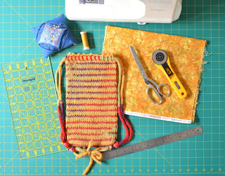 Top view of materials and tools: sewing machine, quilters' rule, pincushion with pins, reel of sewing thread, swatch of cotton fabric, scissors, rotary cutter, steel rule and WIP Project Bag on a cutting mat.