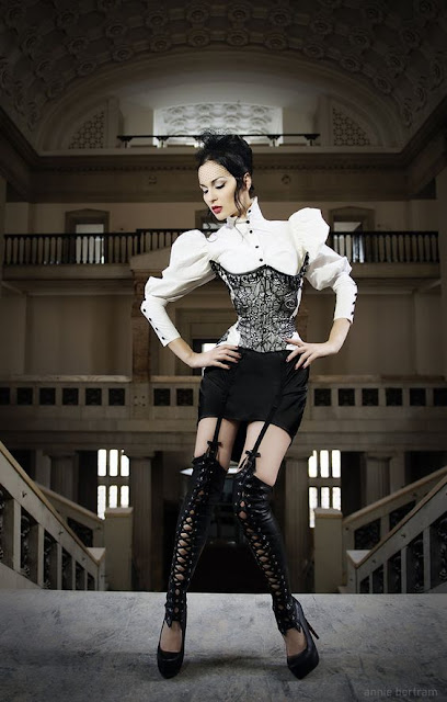 Woman wearing sexy modern victorian influenced (neo-victorian) clothing. Black mini skirt, white blouse with leg of mutton sleeves, underbust corset, and thigh high lace up leather boots with attached garters and cut outs.
